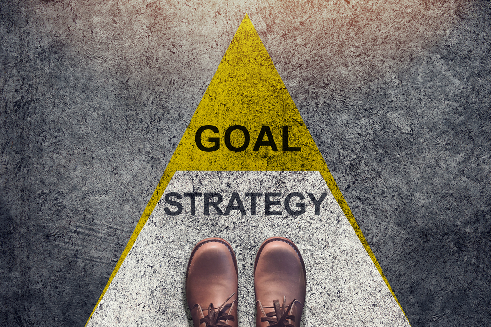 """Goal strategy"" sign on the ground and shoes."