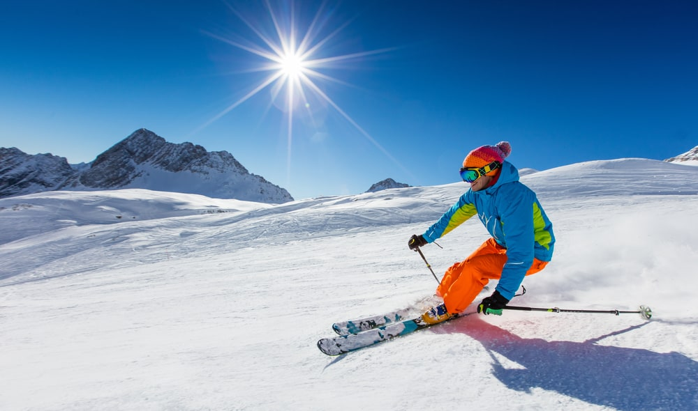 Skier on the slope and the sun in the background